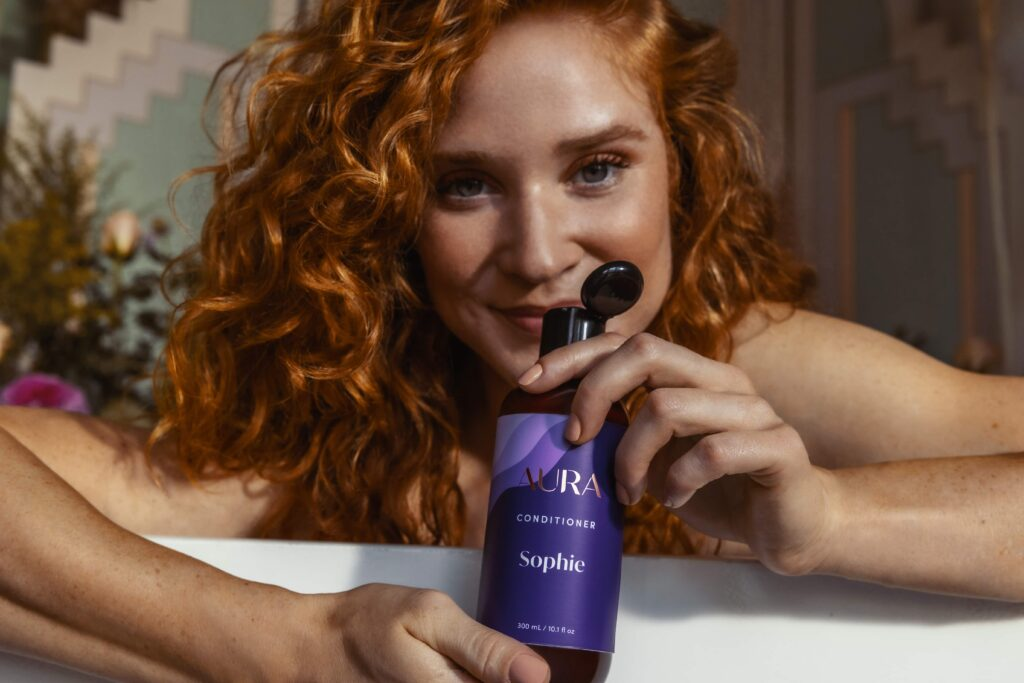 Image of AURA model smelling her personalized hair care Ritual products, made with one of five signature aromas.