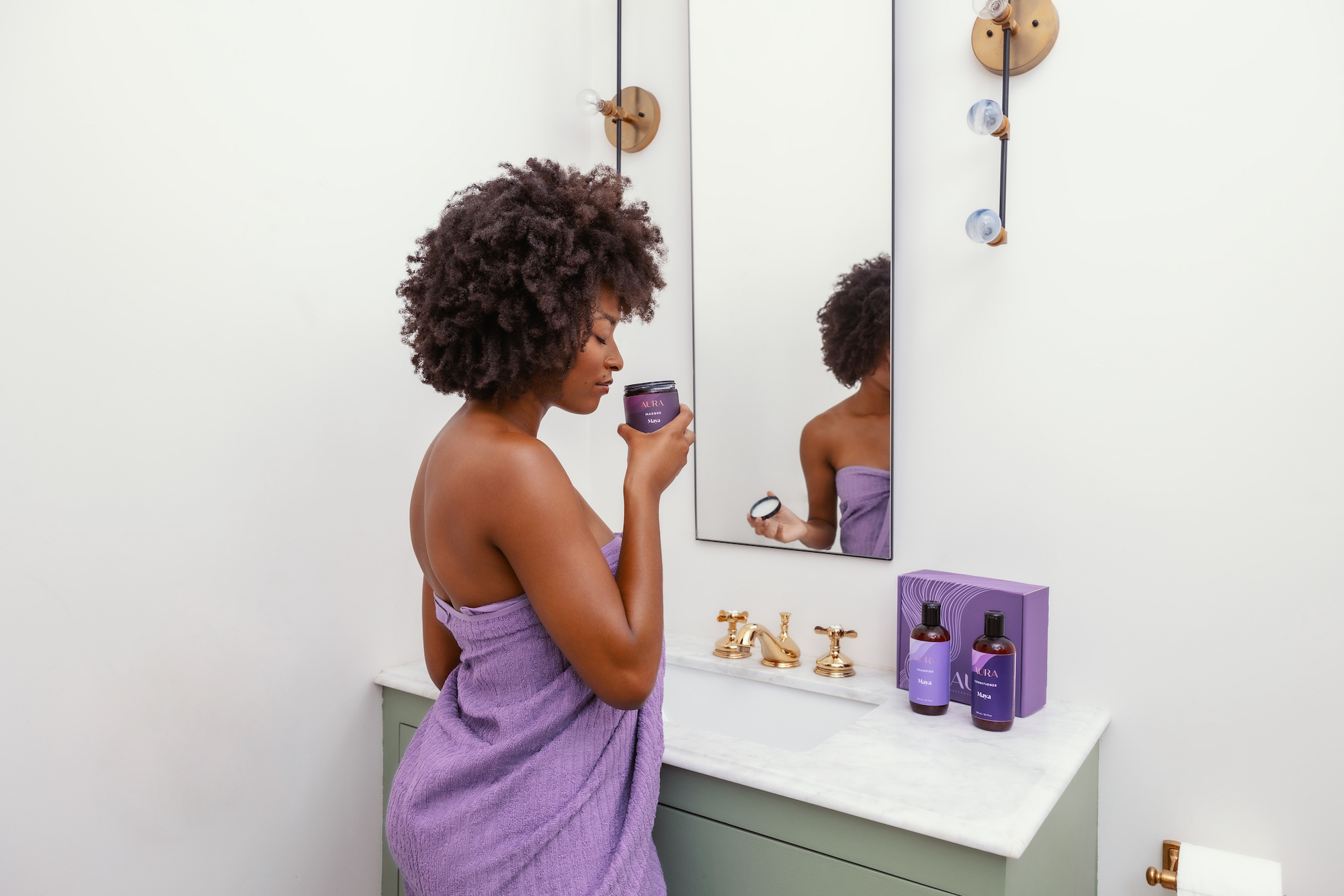 AURA client getting ready to use her personalized Ritual complete with Shampoo, Conditioner, and hair Masque while enjoying her optional aroma.