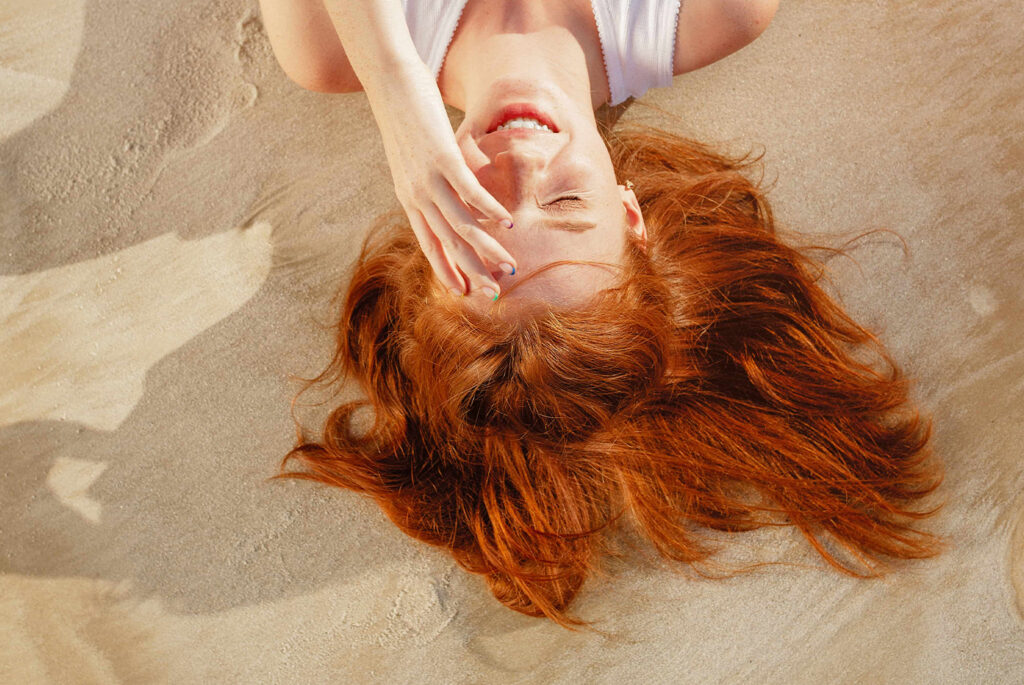Girl laying in the sand, shielding her face from the sun.