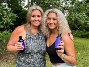 Ariana Adams and her Mom, Sandi, holding their AURA bottles
