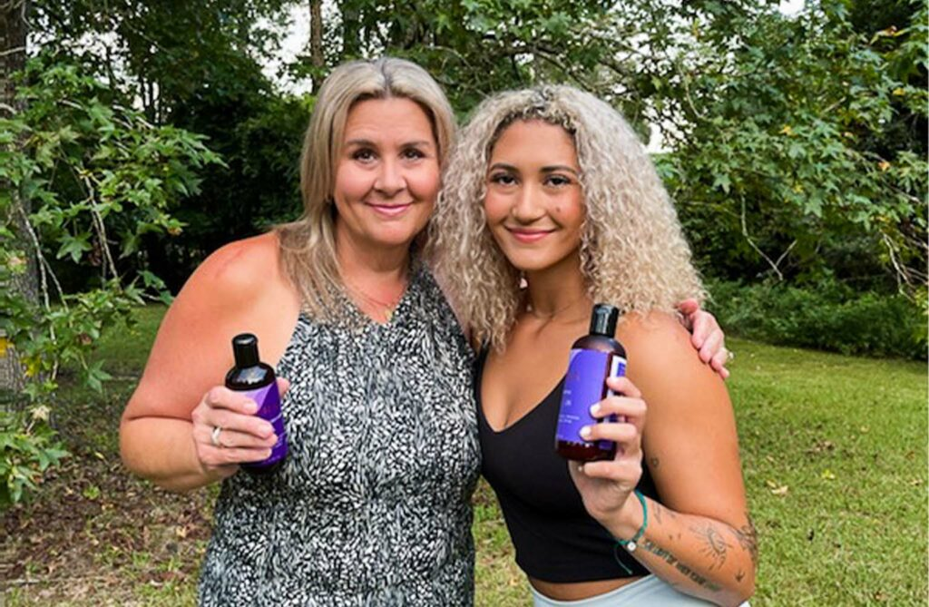 Ariana Adams with her Mom, Sandi, holding their AURA bottles and smiling