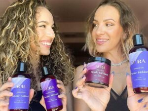 Natalie and Nicole Kirkland looking at each other, smiling, while holding their AURA personalized hair care Ritual