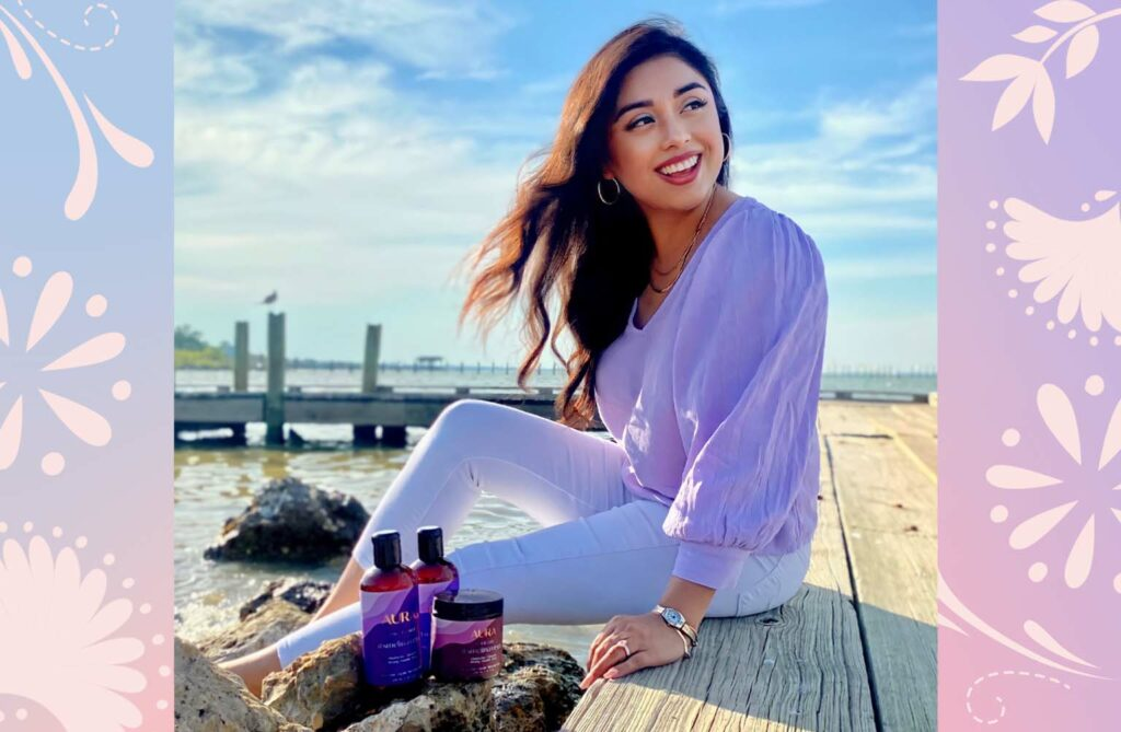 Melina Vega sitting by the water with her personalized AURA hair care Ritual including Shampoo, Conditioner, and hair Mask.